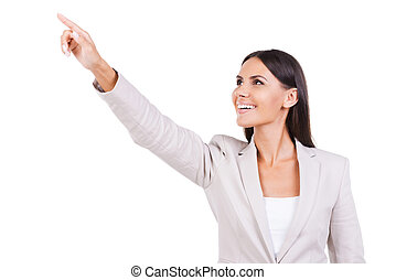 Look over there! Curious young businesswoman in suit pointing away and smiling while standing against white background