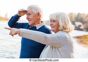 Look over there! Happy senior couple standing on the quayside together while woman pointing away and smiling