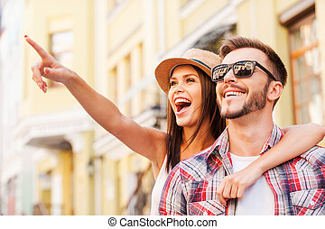 Look over there! Happy young loving couple bonding to each other while beautiful woman pointing away and smiling