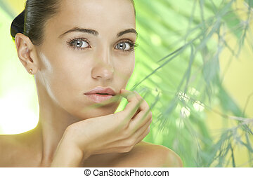 look - portrait of young beautiful woman on green leafs back