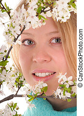 Look through spring flowers - Smiling blonde woman behind...