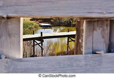 Look through wooden fence on to a lake