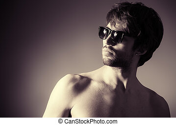 look through sunglasses - Handsome shirtless young man...