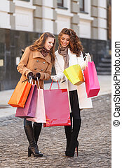 Look what I've got! Full length of two beautiful young women checking the shopping bags