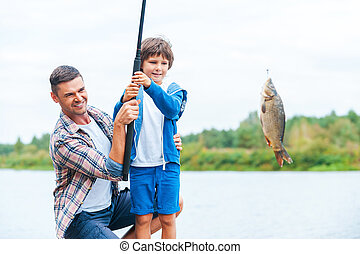 Look what we caught! Father and son stretching a fishing rod...