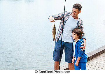 Look what we caught! Father holding fishing rod and showing...