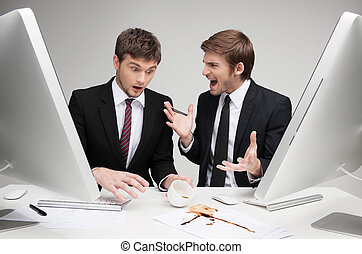 Look what you've done! Two angry young business people arguing while sitting at the working place