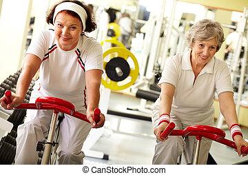 Two pretty senior women in health club