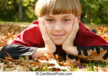 Looking Ahead - A boy laying in a park with his head in both...
