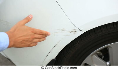 looking at a damaged vehicle. man inspects car damage after an accident