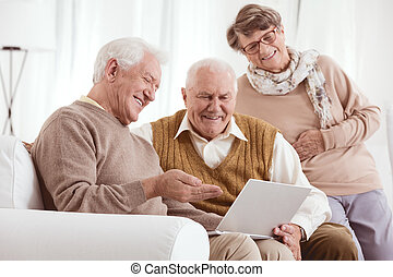 Looking at old photos - Two older men and a woman looking at...