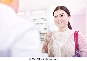 Smiling happy woman looking at the pharmacist in white uniform