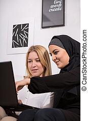 Looking at photos - Muslim and caucasian girls looking at ...