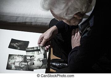 Looking at photos - Senior depressed man looking at old ...