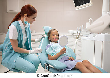 Girl looking at her teeth into mirror while visiting dentist