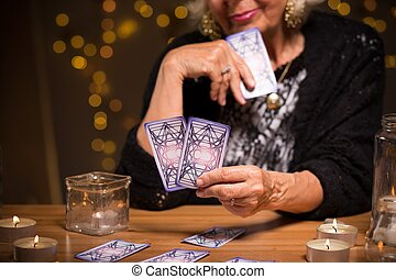 Looking at the cards - Old fortune teller is looking at the...
