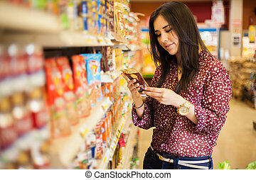 Looking at the food label - Cute young woman examining a...