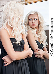 Looking at the mirror. Attractive young blond hair woman in ...