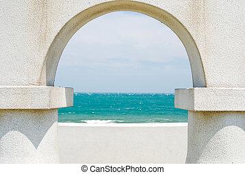 looking at the ocean through arch door