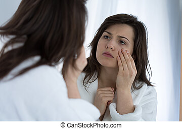 Looking at wrinkles - Young sad woman looking in the mirror...