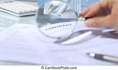 looking contract, magnifying glass - looking through a...