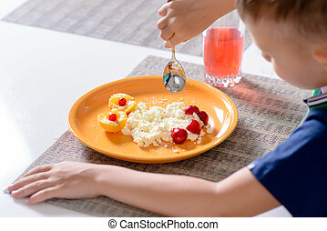 Young Boy Eating Plate of Cheese and Fruit