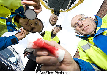 looking down - First aid team looks down to patient