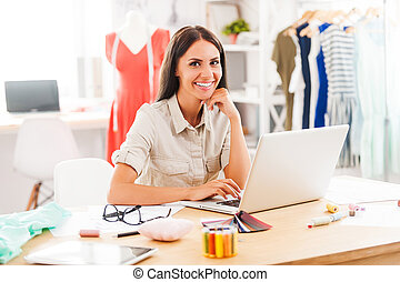 Looking for design inspiration online. Cheerful young woman holding hand on chin and smiling while sitting at the desk in her workshop