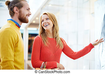 Woman showing something to handsome young man at shopping window