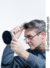 Looking for gray hair - Guy checking out his hair with a...
