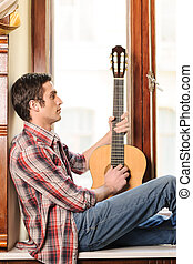 Looking for inspiration. Handsome young man sitting on the windowsill and holding an acoustic guitar in his hand