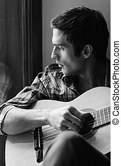 Looking for inspiration outside. Black and white shot of man playing guitar and looking through window