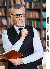 Looking for inspiration. Thoughtful grey hair senior man in formalwear holding note pad and looking away while leaning at the table and with bookshelf in the background