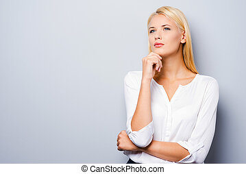 Looking for inspiration. Thoughtful young women holding hand on chin while standing against grey background