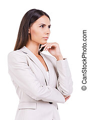 Looking for inspiration. Thoughtful young businesswoman in suit holding hand on chin and looking away while standing against white background