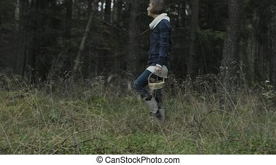 Looking for mashrooms in forest - Young woman is walking on...