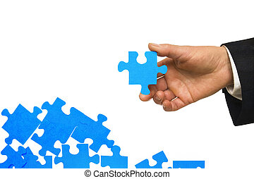 Looking for solution - A man's hand holding a blue piece of...