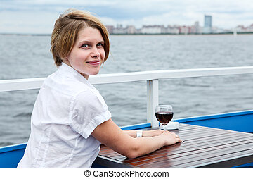 Looking from back woman with red wine glass at the cafe table