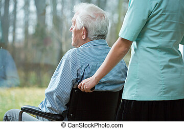Nurse and handicapped man looking from the window