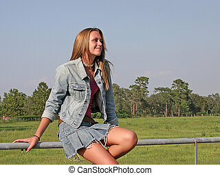 Looking Heavenward - A beautiful girl sitting on a fence in...
