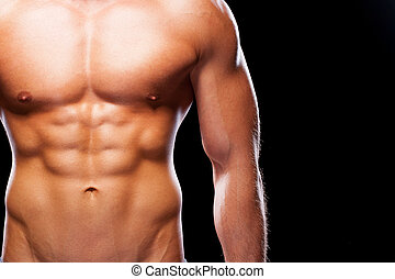 Looking ideal. Close-up of young muscular man with perfect torso standing against black background
