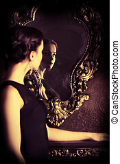 looking into mirror - Beautiful elegant lady stands by the...