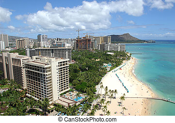 Looking out across Waikiki Beach to Diamond Head with sunbathers enjoying the sand and surf.