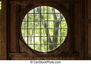 Looking out from inside an open building with round windows...