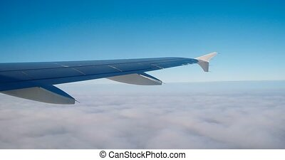Looking out of window of a plane to the aircraft wing, blue sky and clouds beneath