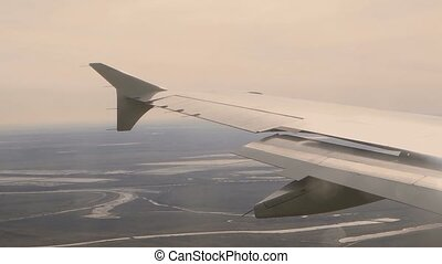 Looking out of window of a plane to the aircraft wing,earth, river beneath