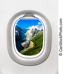 Looking out the window of a plane to the mountains and glacier