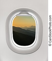 Looking out the window of a plane to the mountains and...