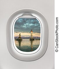 Looking out the window of a plane to the lighthouse in...