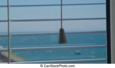 Looking out through the open window blinds at sea with floating boat